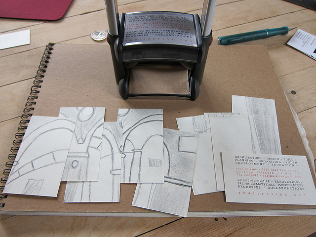 Image of a pile of business cards and the rubber stamp they were made with